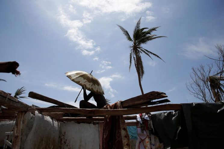 A man sits covering himself with an umbrella on the roof of a house affected by Hurricane Matthew in Port-a-Piment, Haiti. REUTERS/Andres Martinez Casares